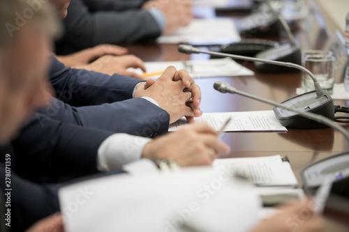 Foto One of politician sitting by table with his hands over document during political