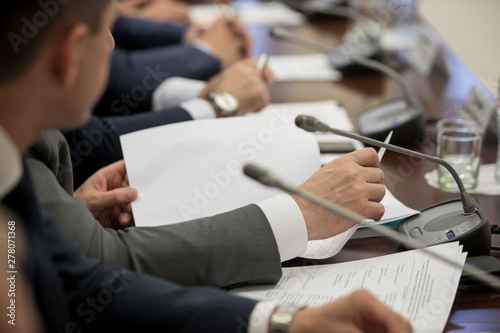One of politician sitting by table with his hands over document during political Fototapete