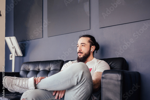 Fényképezés  Handsome young man stylish hipster sitting on the sofa and looking aside