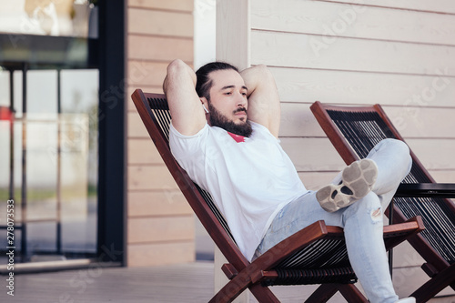 Valokuvatapetti Thoughtful young stylish hipster man with beard resting sitting on the lounge beside the hotel