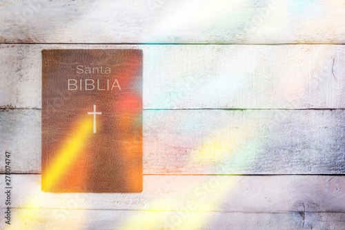 Spanish version of Holy Bible with some stained glass reflection on a wooden table. Top view and empty copy space for Editor's text.