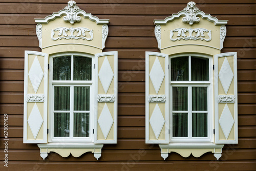 Photo two windows with the wooden carved architrave in the old wooden house in the old Russian town