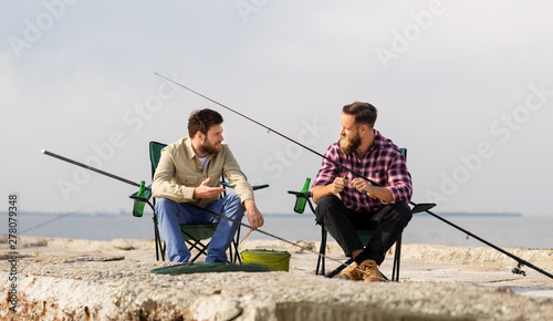 Fotomural leisure and people concept - friends or fishermen adjusting fishing rods with ba