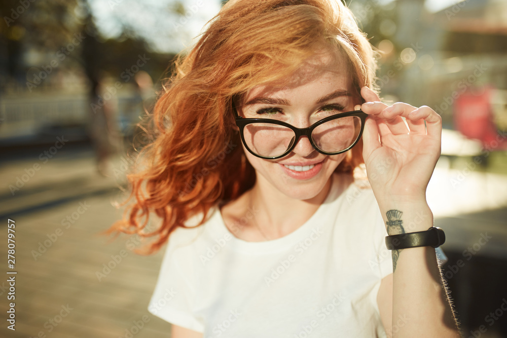 Fototapeta Portraits of a charming red-haired girl with a cute face. Girl posing for the camera in the city center. She has a wonderful mood and a lovely smile