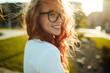 Portraits of a charming red-haired girl with a cute face. Girl posing for the camera in the city center. She has a wonderful mood and a lovely smile