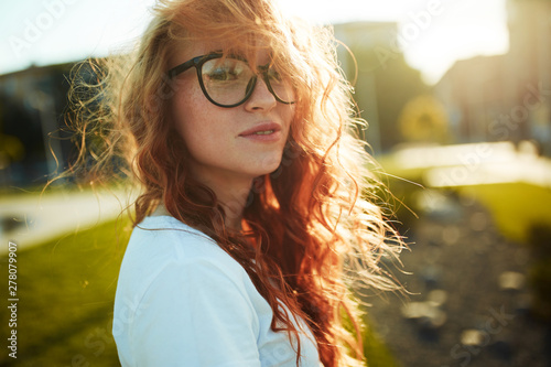 Fototapety, obrazy: Portraits of a charming red-haired girl with a cute face. Girl posing for the camera in the city center. She has a wonderful mood and a lovely smile