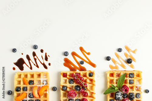 Fotomural  Flat lay composition with belgian waffles and different toppings, top view