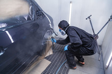 A Male Worker In Jumpsuit And Blue Gloves Paints With A Spray Gun A Side Part Of The Car Body In Black After Being Damaged At An Accident. Auto Service Industry Professions