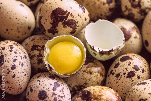 Foto raw quail eggs and broken egg with yolk close-up