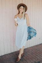 Smiling Woman Wearing White Cami-strap Dress Holding Blue Denim Apparel And Ice Cream While Standing Beside Beige Wall