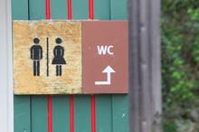 A Toilet Sign In A Public Park
