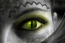 Part Of A Woman's Face In Black And White Color. Green Glowing Eye.