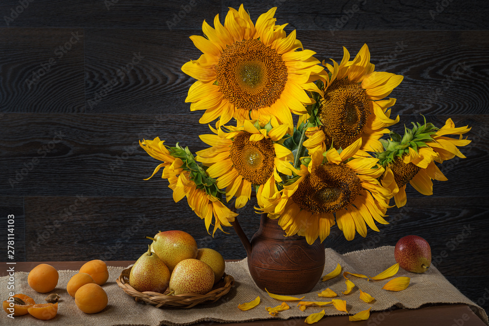 Obraz Still life with sunflowers in a clay pot and fruit on against a wooden wall. fototapeta, plakat