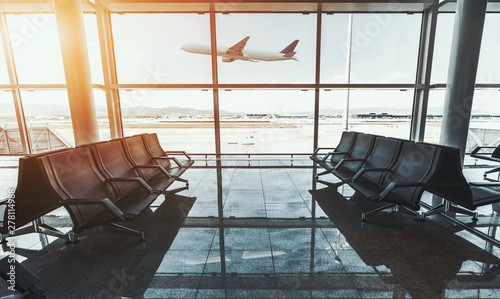 Poster Avion à Moteur Wide-angle shot of a modern aircraft gaining the altitude outside the glass window facade of a contemporary airport terminal waiting room with rows of seats and reflections on a marble floor