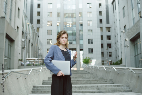 Outdoor portrait of young female enterpreneur standing on stairs of office building holding laptop and coffee Wallpaper Mural