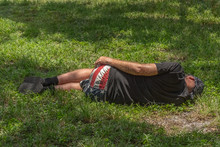 The Forgotten American Sleeps On The Ground At The Park As The Morning Sun Dapples His Body. Wearing Mostly Black Clothing Which Makes His American Flag Shorts Stand Out.