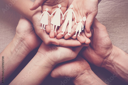 Obraz Adult and children hands holding paper family cutout, family home, adoption foster care, homeless support concept, mental health, Autism support, domestic violence, social distancing - fototapety do salonu
