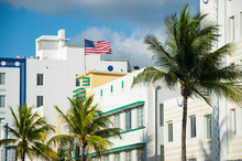 Sunny Scenic View Of American Flag Flying Atop Typical Art Deco Architecture With Tropical Palm Trees On Ocean Drive In South Beach, Miami, Florida