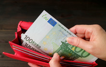 Woman's Hand Taking Euro Banknotes From The Red Wallet