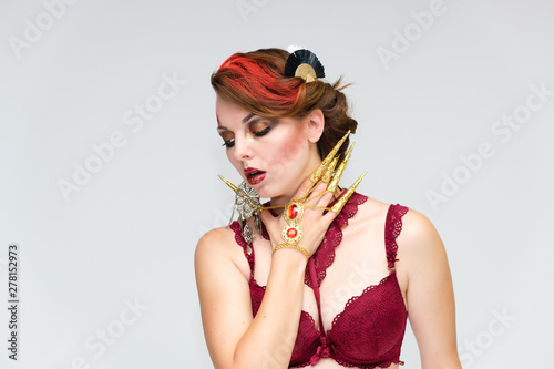 Fototapety, obrazy: Portrait to the waist on a white background of a pretty young brunette woman with beautiful makeup, with gold jewelry on her hand. Beauty, great makeup. Shows emotions.