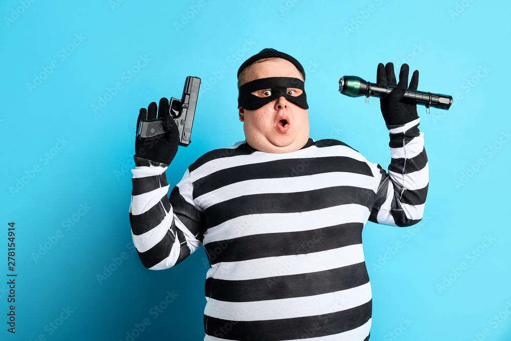 Fototapeta nervous unhappy burglar is being cought by police, isolated blue background. studio shot