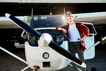Lovely Kid In Aviator Glasses And With Screwdriver Stands With Smile Near Small Single-engine Aircraft With Propeller, Waiting His Father To Come And Help Him With Engine Repair Work.