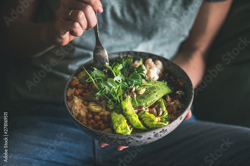 Healthy dinner or lunch. Woman in t-shirt and jeans eating vegan superbowl or Buddha bowl with hummus, vegetable, salad, beans, couscous and avocado - 278169511