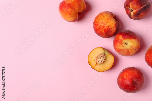 Obraz na płótnie Sweet juicy peaches on pink background, top view. Space for text