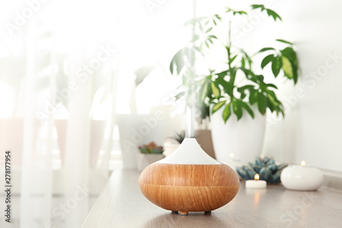 Fototapeta Composition with modern essential oil diffuser on wooden shelf indoors, space for text obraz