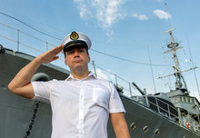Navy Officer Standing Beside Warship And Do Salute.The Captain In White Uniform Stands Under A Battleship And Saluting.