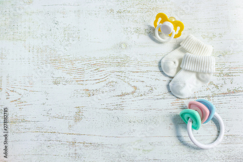 Valokuvatapetti Baby accessories for newborns: socks, toy and soother on light wooden background