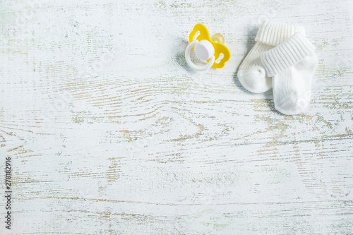 Vászonkép Baby accessories for newborns: socks and soother on light wooden background