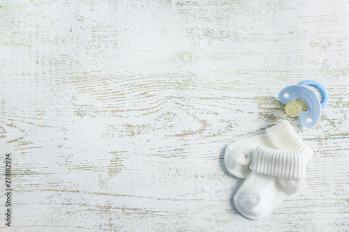 Baby accessories for newborns: socks and soother on light wooden background Canvas-taulu