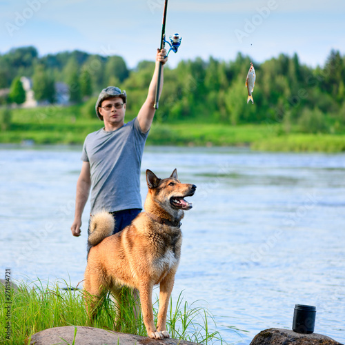 The Caucasian fisherman and his pet are on the riverbank in summer Fototapet