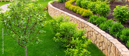 La pose en embrasure Jardin Landscaping in home garden. Beautiful natural landscape design with flower beds in summer. Panoramic view of landscaped part with plants in yard or backyard of residential house.