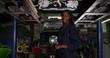 4K Portrait of cheerful Afro American female apprentice in garage workshop. Slow motion.