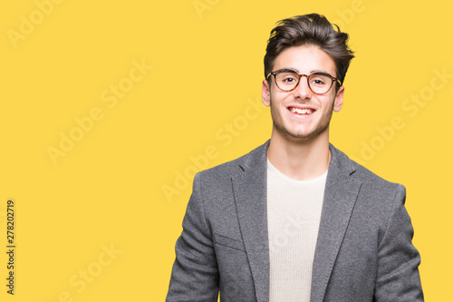 Young business man wearing glasses over isolated background with a happy and cool smile on face Wallpaper Mural