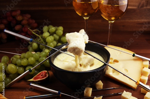 Valokuva  Gourmet Swiss fondue dinner on a winter evening with assorted cheeses on a board