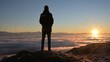 The silhouette of a man stands at sunset above the clouds and contemplates the setting sun. The concept of tranquility and pleasure in traveling