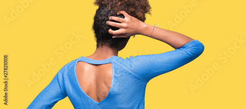 Beautiful young african american woman over isolated background Backwards thinking about doubt with hand on head