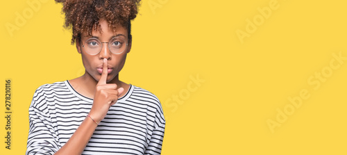 Fotografie, Obraz  Beautiful young african american woman wearing glasses over isolated background asking to be quiet with finger on lips
