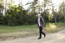 Portrait Of Unshaven Bald European Male Pensioner With Backpack, Carrying Fishery Rod Or Spinning Reel, Going To Catch Fish On River Bank. Recreation Fishing, Active Healthy Lifestyle And Leisure