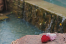 Red And Pink Hearts On Stone With Beautiful Blurred Background Of Waterfall
