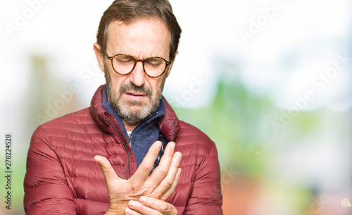 Middle age handsome man wearing glasses and winter coat Suffering pain on hands Canvas Print