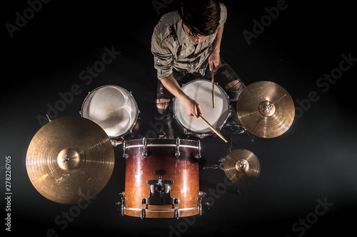 Wallpaper Mural Professional drummer playing on drum set on stage on the black background