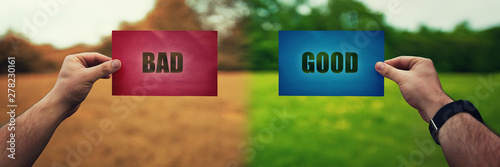 Foto Man hands holding two colored paper sheets with opposite text good and bad over different nature environment background