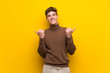 Handsome young man over isolated yellow background with thumbs up gesture and smiling