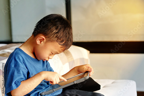 Photo Boy play smart phone tablet in concentration alone in room in family care and AD