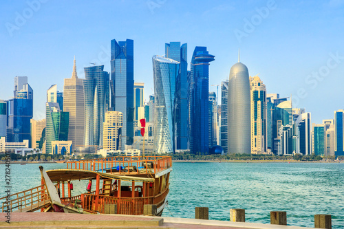 Fényképezés  Traditional wooden dhow on foreground at Doha Bay and skyscrapers towers of West Bay skyline on background