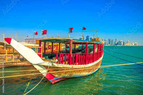 Fényképezés  Perspective view of a traditional wooden dhow with qatari flag in foreground with seafront of Doha Bay and skyscrapers of West Bay skyline